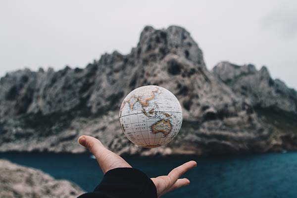 Hand Holding floating globe with mountain background