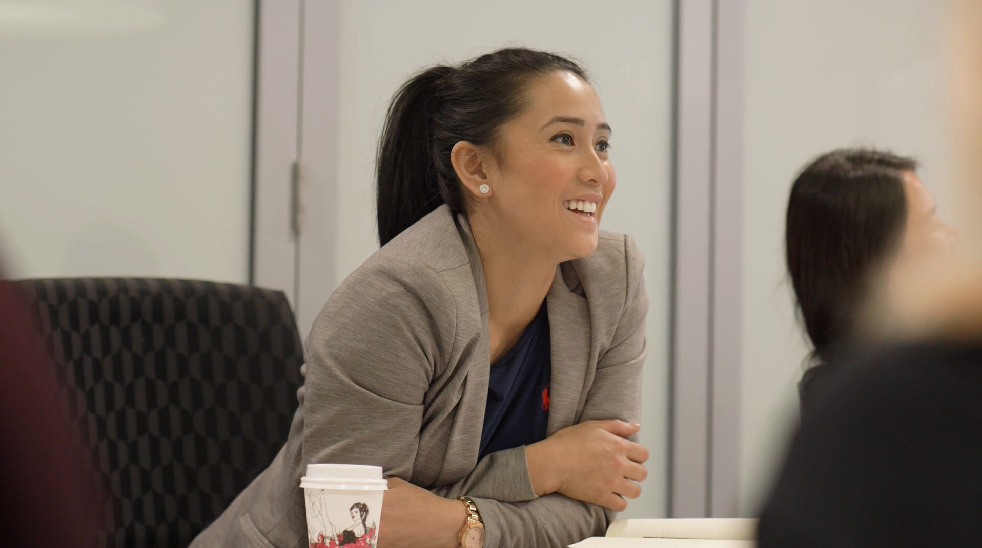 Lady in suit laughing sitting in conference room
